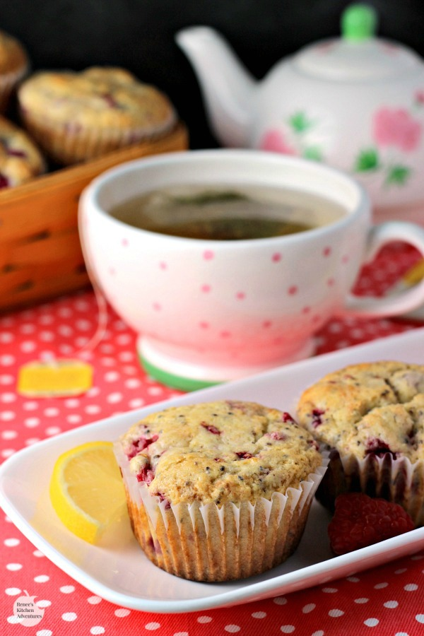 Lemon Raspberry Chia Seed Muffins by Renee's Kitchen Adventures on a white platter with a cup of hot tea in the background and a basket of muffins behind the tea cup