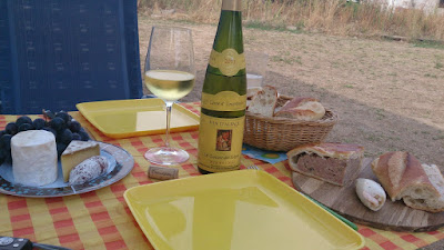 A laid table with wine and groceries from the Alsace.