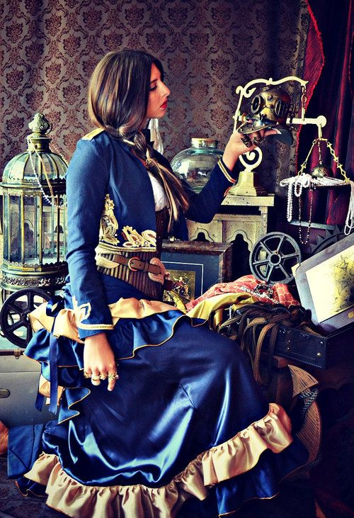 Woman wearing blue and gold steampunk costume. Her clothing: military style bolero jacket, underbust corset, tiered ruffle skirt. Jewelry: rings