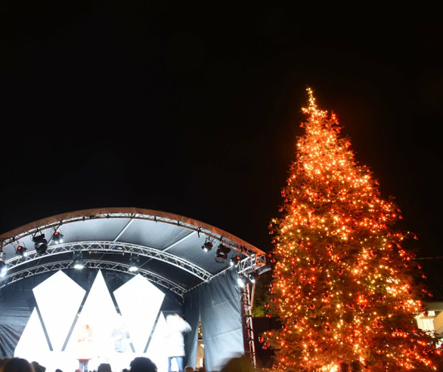 a stage with live music next to a huge christmas tree lit up with lights.