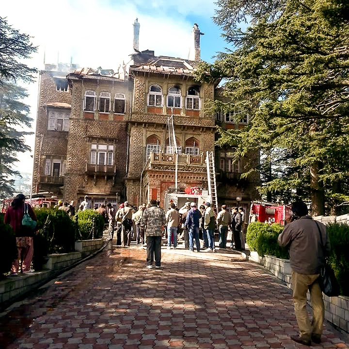 If you have visited Shimla and took a walk from Mall road to Viceregal Lodge, Gorton Castle comes on the left side of the road. A magnificent heritage building near Himachal Pradesh Vidhan Sabha. Gorton Castle was build in British era and was currently in use as office of Accounting General of Himachal Pradesh. It was very sad to hear that one of the most beautiful Heritage building in Shimla changed into ashes overnight. All the photographs shared in this Photo Journey are clicked after the night, when Gorton Castle caught fire.It's a big setback to people of Shimla town and heritage lovers. Top two floors of the building have converted into ashes and some of the photographs here would give a clear sense of loss happened.Gorton Castle is five storey Heritage Building in summer capital of British India , Shimla, which was established in 1904. This was designed and constructed in a Gothic style, the foundation of the building was laid by Sir Swinton Jacob, a renowned British architect. He served a long term as an executive engineer in the Rajputana state of Jaipur.One of the main highlights of Gorton Castle is the 'Rajasthan jaali' work on balconies, which was very well combined with British style architecture. Gorton Castle was also used as Civil Secretariat of the Imperial Government of India.  It's located on a hill adjacent to the road which connects Mall road with Viceregal Lodge or Himachal Pradesh Vidhan Sabha in Shimla. Gorton castle is spread in an area of 400 feet x 100 feet. Gorton Castle is encircled by rosewood like timber blocks which were brought from Andaman Islands. Solid grey Sanjauli stone was used in the construction of the building and a red tile roof, which was replaced by galvanised red iron sheet roof.  Gorton Castle caught fire at around 3am and fire brigade was informed soon after it happened. Fire tenders from Shimla and other surrounding places took quick action along with Army folks. Within few minutes the entire building was under high flames. Some of my friends from Shimla witnessed the sad moment. And there are few videos available on news channels which showed the way Gorton Castle converted into ashes, specially it's top two floors. Fire was brought under control around 10:30am.It seems that fire started from the top floor of Gorton Castle and then it spread to lower parts as well, especially the second last storySome of the early witnesses of this tragedy said the fire may have been caused by short-circuting or use of electric heating, either by the night guards or officials, who may have left heaters on while leaving the office. This thought may make you feel worse that carelessness of employees can cause such a disaster. It seems that lot of heritage buildings of Shimla have gutted in winter fires in past two decades,  but this incident has been a big shock. Probably because of the fact that Gorton Castle is very well located in the town and many of the folksPrincipal AG and DAG officers are shifted to railways building. And whole building will be renovated within in year or so. Renovation initiatives have been started, but it's going to be huge task and not sure how many documents would never be recovered. Wondering how it would impact the normal people of the state, as many of the important files must have been converted into ashes.