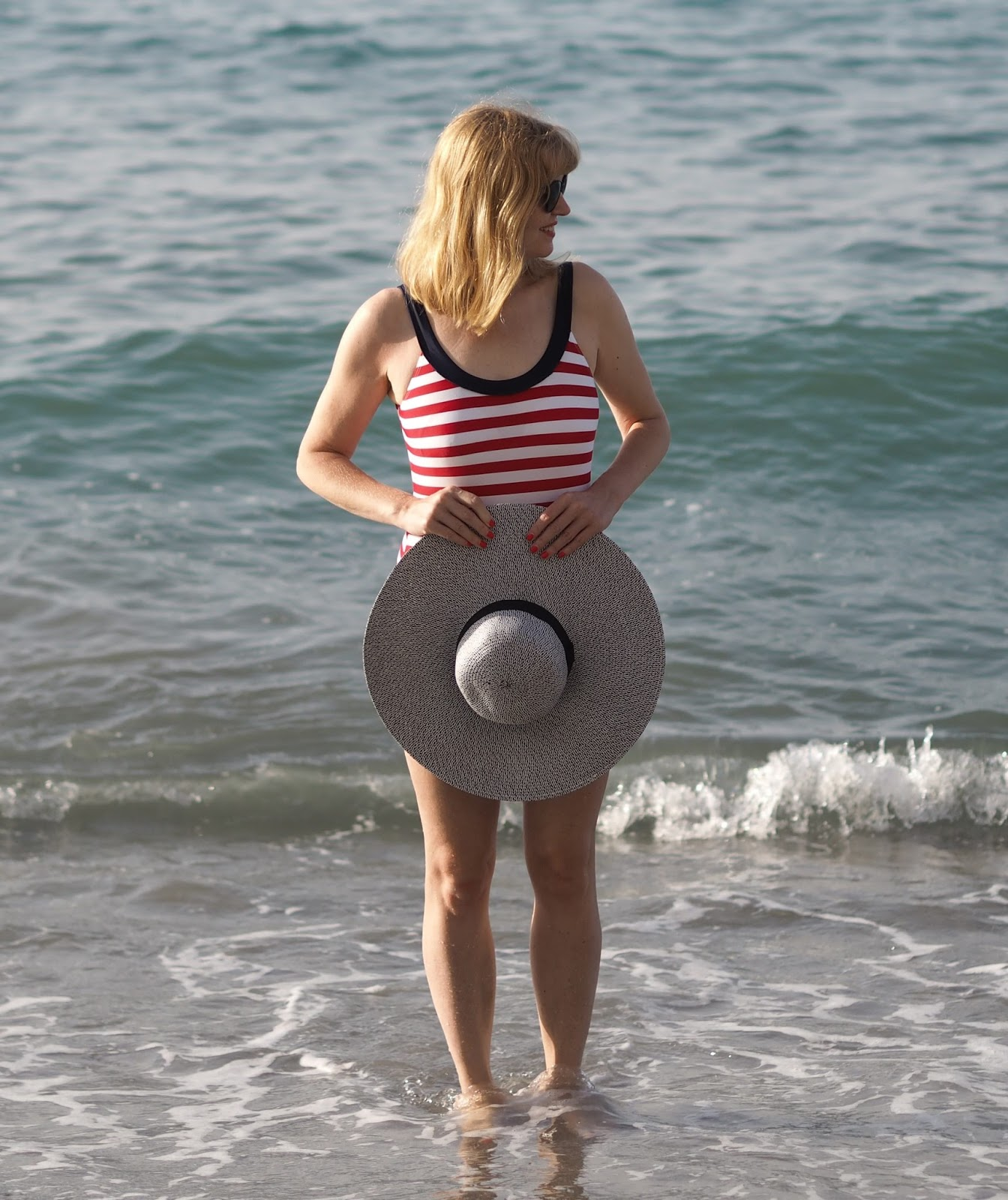 Red striped nautical swimsuit and large floppy straw hat