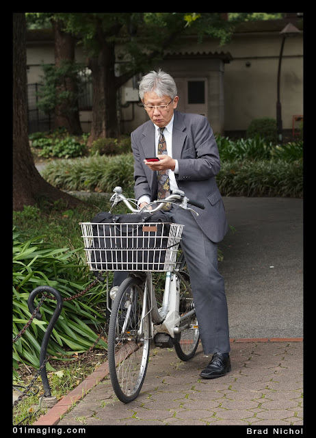 Japanese man on bike in suit with phone in Japanese park, bag in basket, grey suit, bike has electric motor, tokyo, japan.