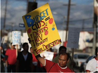 "Photo of African-American man holding up a hand-made sign that reads, ""Budget Cuts = Deaths HIV Poverty Total Devastation"""
