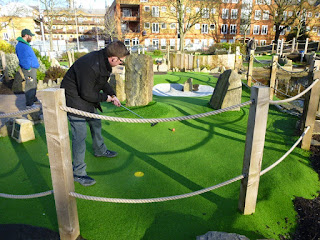Playing the Putt in the Park mini golf course in London as Pat Sheridan from the Putting Penguin looks on
