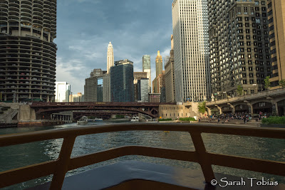From the bow of the Water taxi, the boat rails, water, bridges and tall buildings on either side.