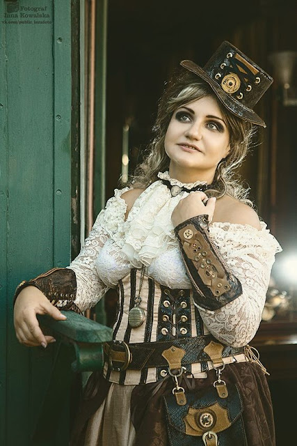 Woman wearing steampunk clothing including a cream lace blouse and brown leather top hat