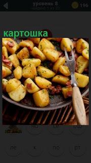 приготовленная картошка на сковородке с вилкой