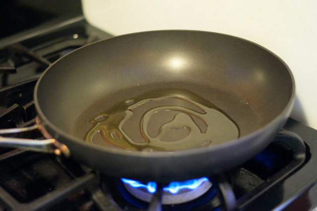 Non-stick frying pay with coconut oil over flame on the stove.