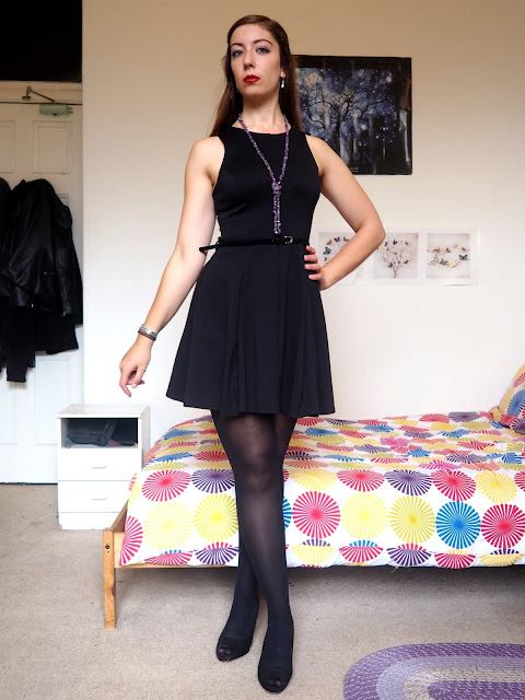 Maleficent inspired Disneybound outfit of little black dress with tights & high heels, and green & purple jewellery