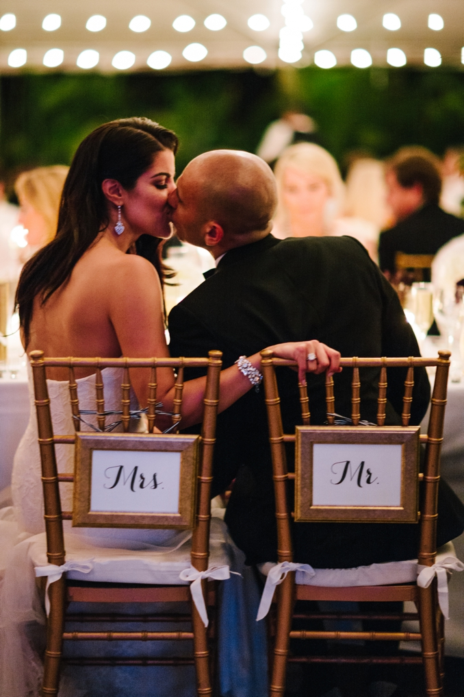 the bride and groom share a kiss during dinner