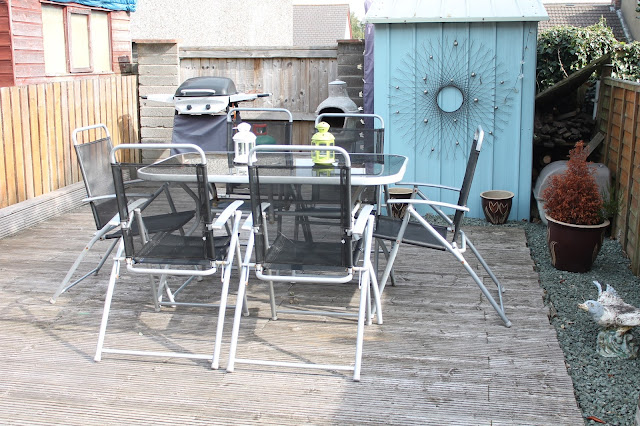 black table and chair set on decking, pale blue shed
