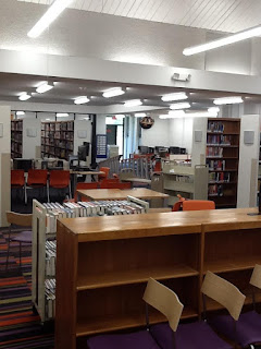 Interior photo of Aspen Hill library showing a low bookshelf, tables, and chairs