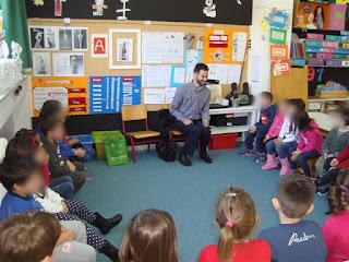 Ο Βαγγέλης χαμογελαστός ακούει τις ερωτήσεις των παιδιών