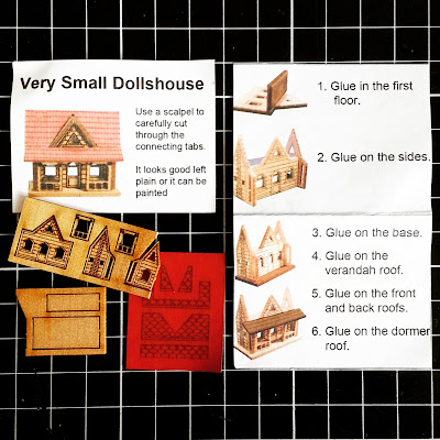 Pieces of a 'Very small dollshouse' and instruction sheet, arranged on a cutting board.
