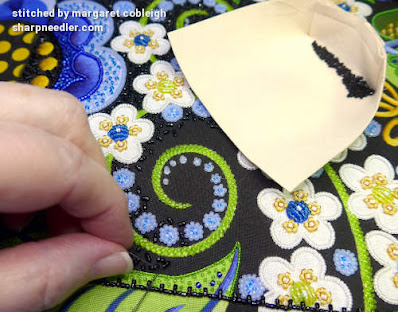 Embroidering the black beaded background with black beads and also showing the bead holder with the beads. (Wild Child Japanese Bead Embroidery by Mary Alice Sinton)