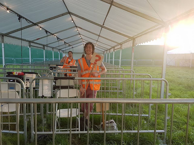 Two stewards at ticket gates whilst volunteering at Glastonbury