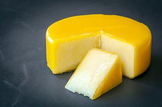 Aged cheddar cheese wheel