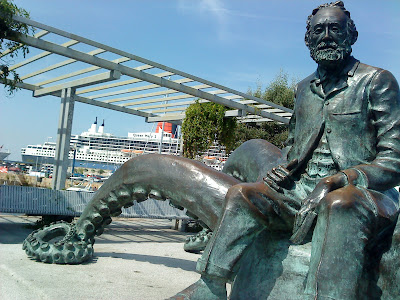 "The statue in honor of the French novelist Jules Verne and his book ""20,000 miles under the sea"" and in the background, the cruiser ""Queen Mary 2"" docked in the port of Vigo (E.V.Pita, 2012)"