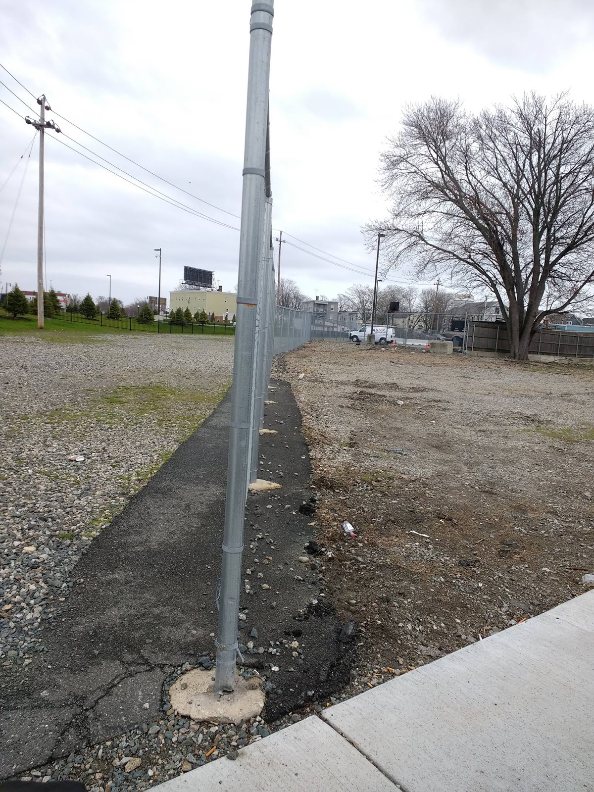 a fence in the middle of the lynn ma rail corridor