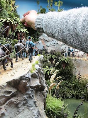 Man placing a piece of miniature toetoe grass into a diorama bush scene.