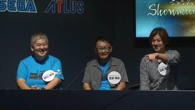 Masaya Matuskaze (right) reacts when he notices someone wearing a Shenmue T-shirt. Next to him are Eigo Kasahara (center) and Hiroshi Noguchi (left).