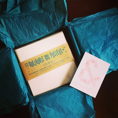 Box of dollhouse gig posters nestled in tissue paper in a postal box.