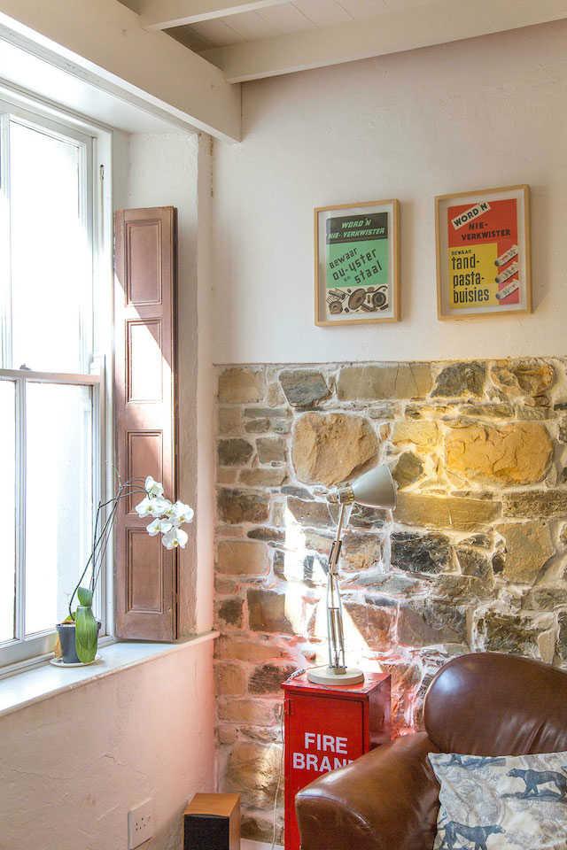 La Grenadine un viaje a Gardens Ciudad del Cabo, salón con pared de piedra y contraventanas pintadas