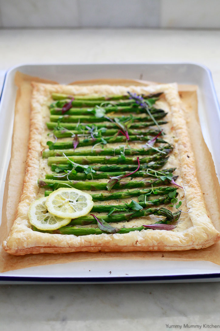 A beautiful asparagus tart on puff pastry topped with two lemon slices and fresh microgreens. This easy asparagus tart is a perfect spring, Easter, or Mother's Day appetizer.