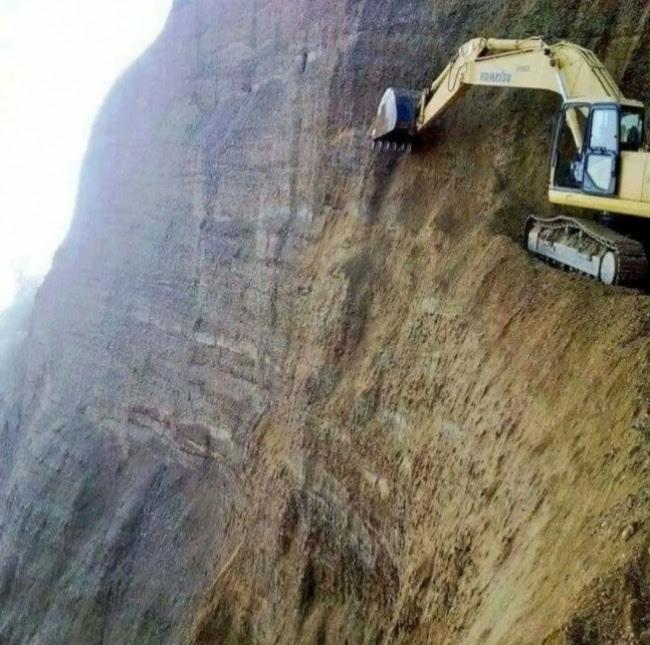 Una excavadora obrint-se camí en un mur vertical de terra que sembla suelta, de debó que fa por.