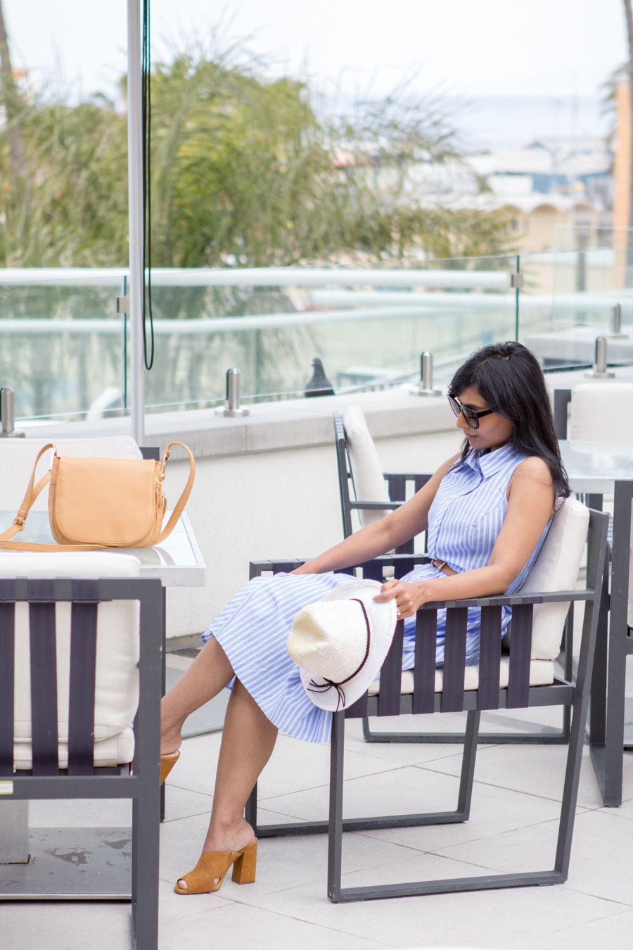 vacation wear, holiday dressing, poolside with cocktails, relaxed dressing, chic dress, belted dress, shirtdress, panama hat, express runway, pearl earrings, stella mccartney, square sunglasses, relaxing by the pool, mules, mustard slides, vince camuto