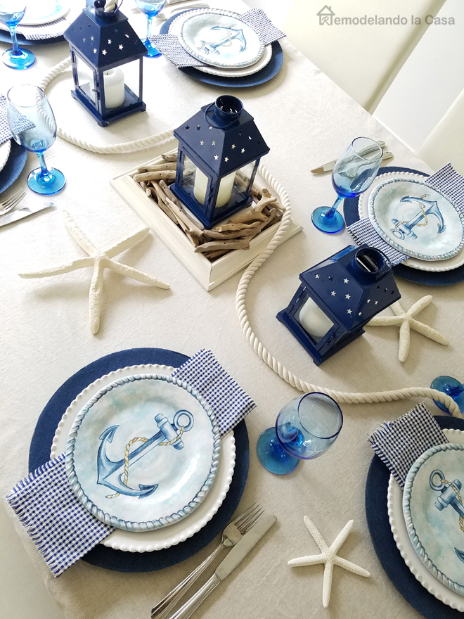 Ginham napkins, anchor salad plates from Wegmans, blue water glasses, blue lanterns, white nautical rope, driftwood pieces