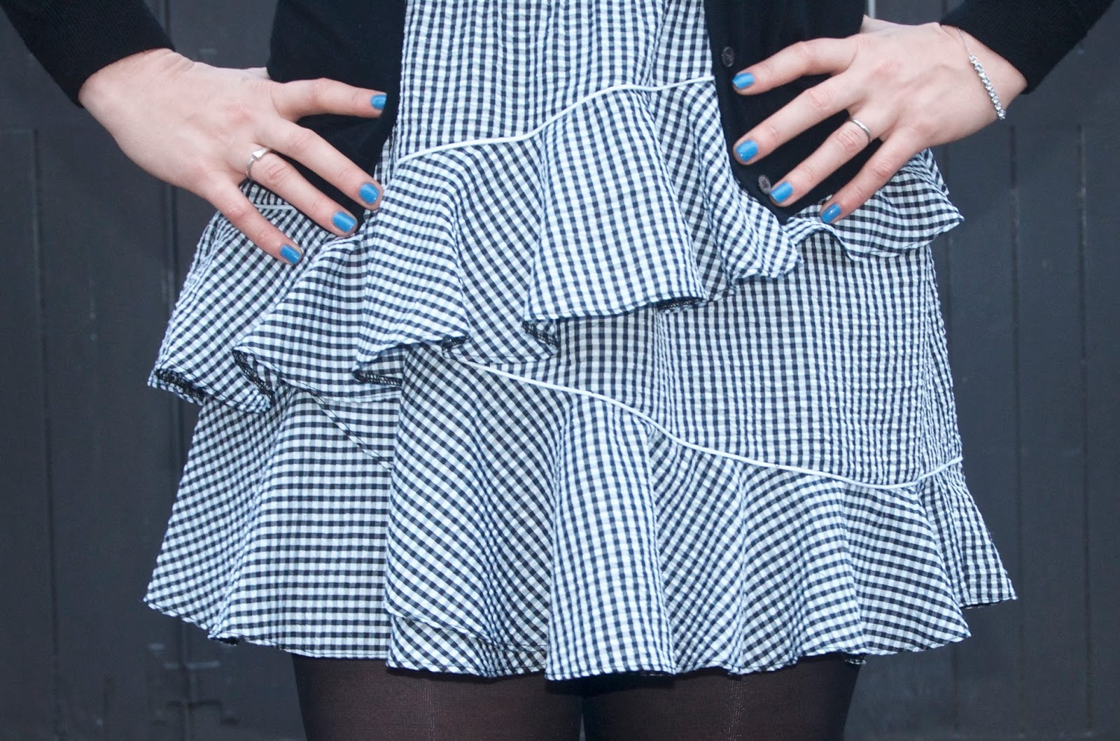 blue nail polish and ruffled skirt