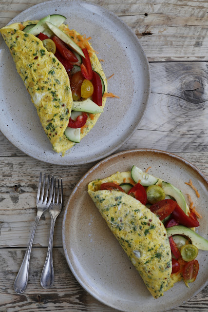 Two plates with omelettes on a wooden background