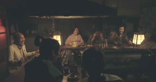 una barra de un bar mitad contemporánea mitad época Edo, vemos samuráis y mujeres en kimono comiendo y también al protagonista vestido con ropa moderna riéndose feliz
