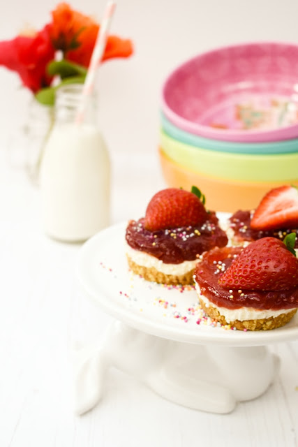Mini no-bake strawberry cheesecakes topped with half a strawberry & spinkles