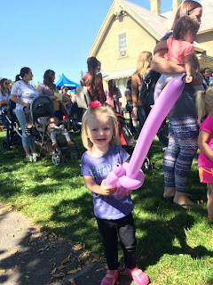 A young girl holding up her Balloon Sword with a happy face