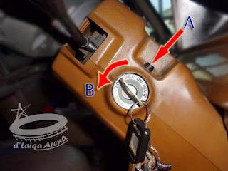 tahan tombol (A) dan putar kunci ke posisi LOCK (B)