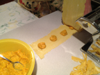 image of top sheet of pasta being carefully laid on top of the sheet with the filling