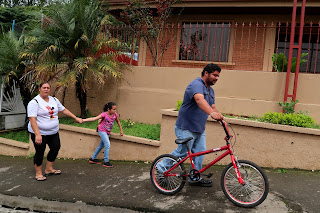 Man pushing daughter's bicycle uphill in Puriscal.