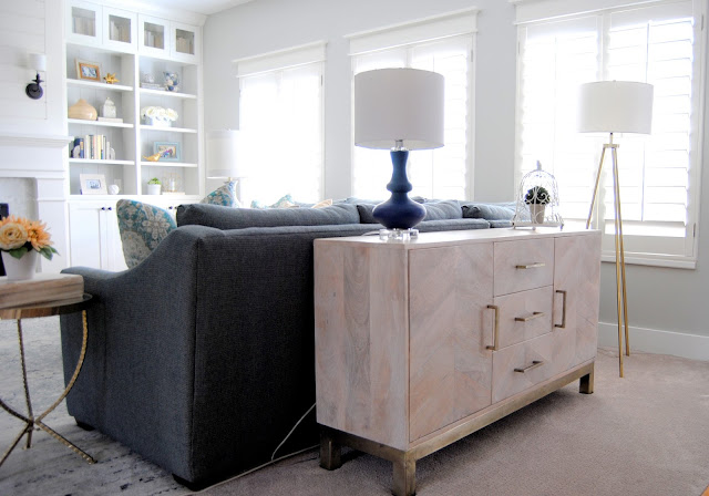 buffet, reclaimed wood, brass, table, round table, side table, tripod lamp, floor lamp, club chair, navy chair, blue chair, suburst mirror, white cabinet, mantel, white mantel, sconces, shiplap, shiplap mantel, mantel makeover, fireplace makeover, fireplace, two tone cabinets, banister, railing, gray, navy, sectional, gray sectional, custom sectional, gas fireplace, mixed metals, built ins, traditional, vintage rug, brass pulls, new carpet, gold