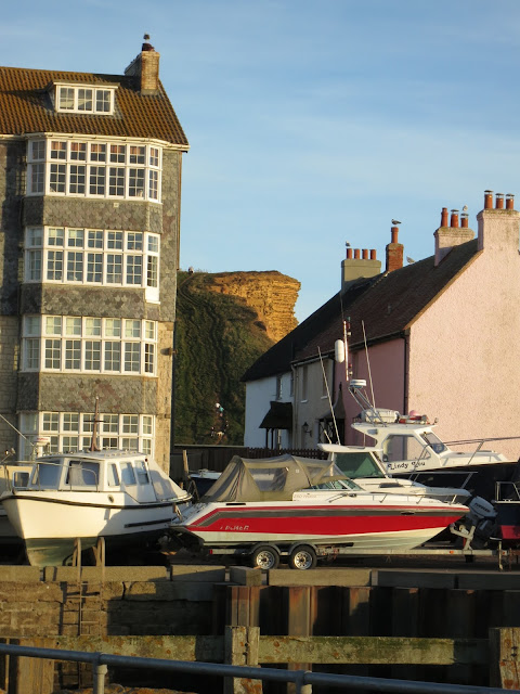 End of eastern cliffs at West Bay seen between block of flats and row of cottages, with boats in the foreground. Dorset