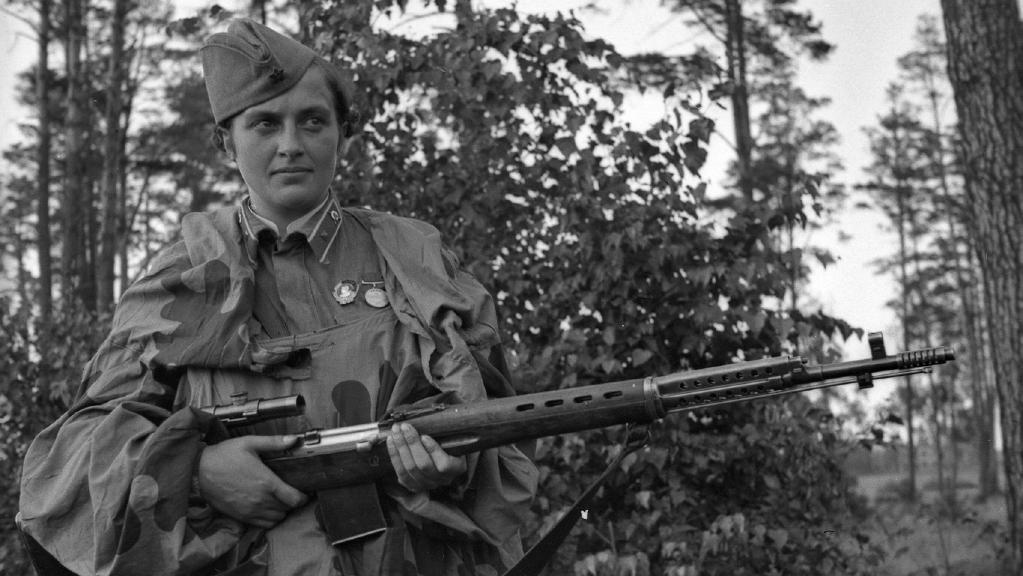 Lyudmila Pavlichenko wearing her uniform holding a rifle standing among trees.