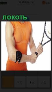 Девушка в руках держит ракетку для тенниса, локоть правой руки перевязан