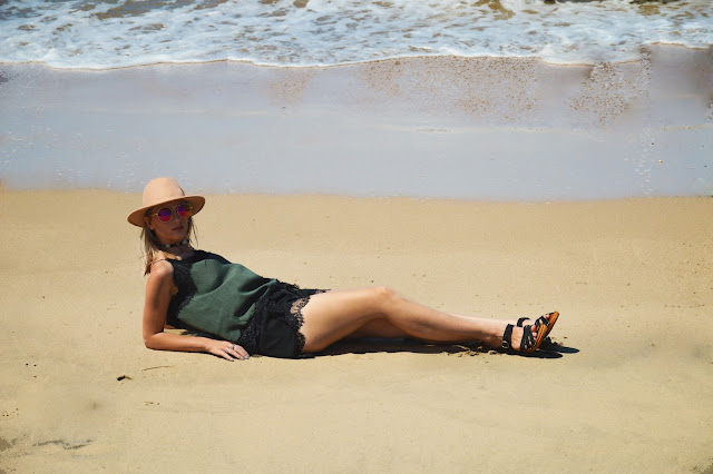 boho girl lying on tropical beach wearing lace cami slip lace shorts round reflective sunglasses