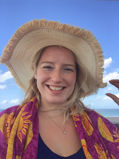 Me in a silly straw hat with a sarong round my shoulders with the sea in the background