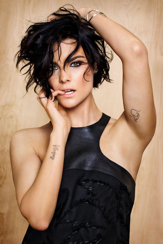 Vemos a modelo de pelo corto en pose seductora con tatuajes pequeños