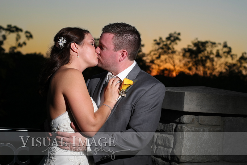 Bride and groom kissing with sunset at The Legend of Brandybrook