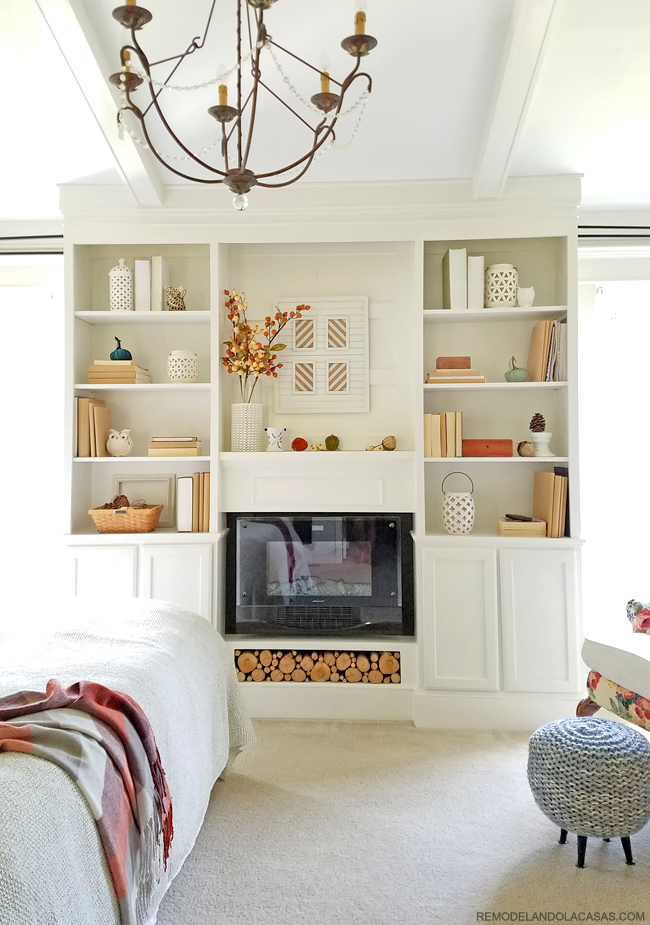 white built-ins with lanterns, brown books and fall branches.
