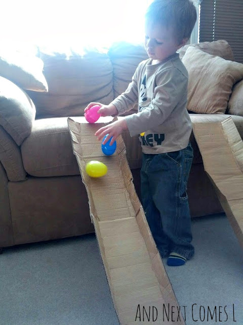 J putting wobbly Easter eggs on to a cardboard ramp from And Next Comes L
